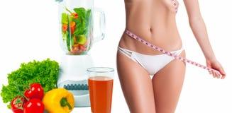 Mujer que mide su cuerpo con una cinta de la medida Concepto de la dieta, verduras frescas imagen de archivo