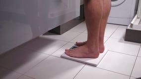 Mujer que mide su peso en una báscula de baño almacen de video