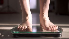 Mujer que mide su peso usando escalas en piso de madera Dieta sana metrajes