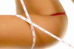 Mujer que mide su pierna Foto de archivo libre de regalías