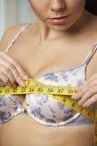 Mujer que mide su talla de sujetador con cinta métrica Fotos de archivo