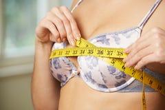 Mujer que mide su talla de sujetador con cinta métrica imagen de archivo