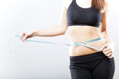 Mujer que mide su vientre después de ejercicio Imagenes de archivo