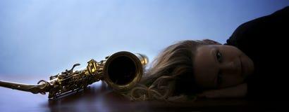 Mujer que miente al lado del saxofón fotos de archivo