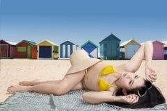 Mujer que miente cerca de las chozas de la playa Imagen de archivo