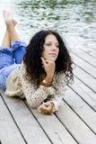 Mujer que miente cerca del río Fotos de archivo