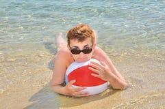 Mujer que miente en agua de mar baja Fotos de archivo