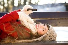 Mujer que miente en banco con el teléfono móvil Imagen de archivo libre de regalías