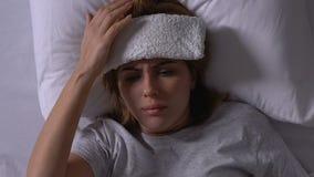 Mujer que miente en cama con la toalla en la frente, tomando píldoras, tratamiento frío, enfermedad metrajes