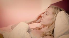Mujer que miente en cama con un dolor de cabeza que frota el lado de su cara almacen de video