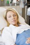 Mujer que miente en cama de hospital Imágenes de archivo libres de regalías