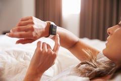 Mujer que miente en cama mientras que comprueba la aptitud App en el reloj elegante Imágenes de archivo libres de regalías