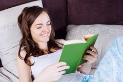 Mujer que miente en cama mientras que lee un libro Fotografía de archivo