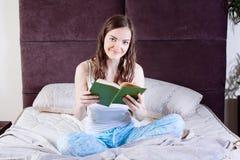 Mujer que miente en cama mientras que lee un libro Imágenes de archivo libres de regalías