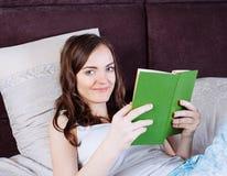 Mujer que miente en cama mientras que lee un libro Fotografía de archivo libre de regalías