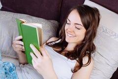 Mujer que miente en cama mientras que lee un libro Fotos de archivo libres de regalías