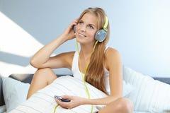 mujer que miente en cama mientras que música que escucha a través del auricular Imagenes de archivo