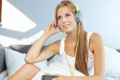 mujer que miente en cama mientras que música que escucha a través del auricular Foto de archivo libre de regalías