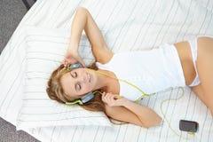mujer que miente en cama mientras que música que escucha a través del auricular Fotografía de archivo