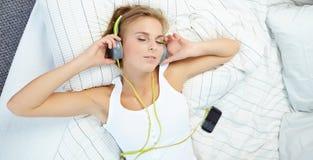 mujer que miente en cama mientras que música que escucha a través del auricular Fotos de archivo