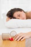 Mujer que miente en cama por la botella derramada de píldoras en la tabla fotografía de archivo libre de regalías