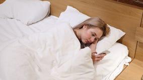 Mujer que miente en cama usando Smartphone para hojear metrajes