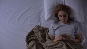 Mujer que miente en cama y que lee el mensaje del amante, soledad, top-vista de las malas noticias almacen de video