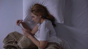 Mujer que miente en cama y que lleva a cabo la prueba de embarazo, observación gritadora en los malos resultados almacen de video