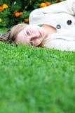 Mujer que miente en campo de hierba en el parque Imágenes de archivo libres de regalías