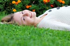 Mujer que miente en campo de hierba en el parque Imagen de archivo