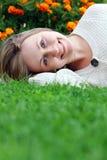 Mujer que miente en campo de hierba en el parque Fotografía de archivo