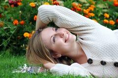Mujer que miente en campo de hierba en el parque Fotos de archivo