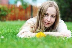 Mujer que miente en campo de hierba en el parque Imagen de archivo libre de regalías
