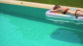 Mujer que miente en el flotador de la piscina y disfrutar de verano almacen de metraje de vídeo