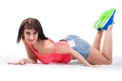 Mujer que miente en el piso aislado sobre blanco Imagen de archivo libre de regalías