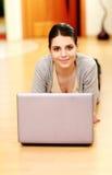 Mujer que miente en el piso con el ordenador portátil Foto de archivo