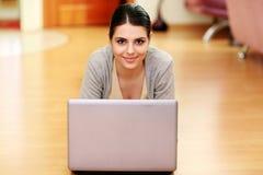 Mujer que miente en el piso con el ordenador portátil Fotografía de archivo libre de regalías