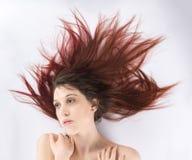Mujer que miente en el piso con el pelo Windblown Imágenes de archivo libres de regalías