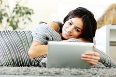 Mujer que miente en el piso con las almohadas y que usa cálculo de la tableta Imagen de archivo libre de regalías
