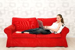 Mujer que miente en el sofá con la computadora portátil Imagen de archivo