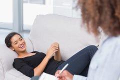 Mujer que miente en el sofá de los terapeutas que parece feliz Foto de archivo