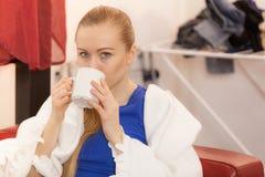 Mujer que miente en el sofá debajo de té de consumición de la manta Foto de archivo libre de regalías