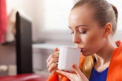Mujer que miente en el sofá debajo de té de consumición de la manta Imágenes de archivo libres de regalías