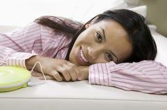 Mujer que miente en el sofá que escucha la música Foto de archivo libre de regalías