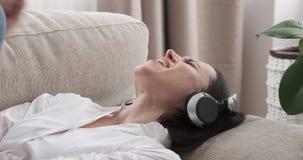 Mujer que miente en el sofá y que canta mientras que música que escucha en los auriculares almacen de metraje de vídeo