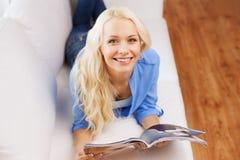 Mujer que miente en el sofá y que lee la revista en casa Imagen de archivo libre de regalías