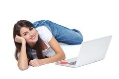 Mujer que miente en el suelo con la computadora portátil Fotografía de archivo libre de regalías