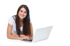 Mujer que miente en el suelo con la computadora portátil Foto de archivo