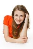 Mujer que miente en el suelo del estudio que sonríe en usted Imágenes de archivo libres de regalías