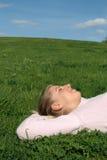 Mujer que miente en hierba Fotos de archivo